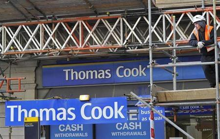 A construction worker stands on scaffolding in front of a branch of Thomas Cook in London December 14, 2011. REUTERS/Toby Melville