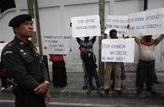 A policeman stands guard near a group of Rohingya people living in Thailand holding signs as they protest in front of Myanmar's embassy in Bangkok, during Myanmar's President Thein Sein visit to Thailand July 23, 2012. REUTERS/Chaiwat Subprasom
