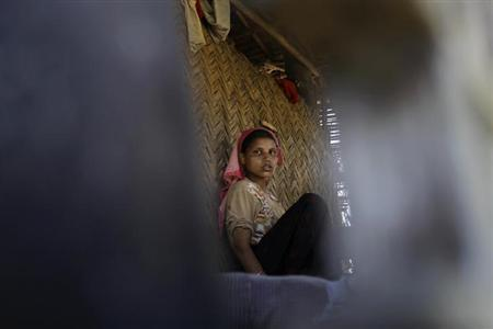 A Muslim woman is reflected in a mirror inside her house in Paik Thay village, the site of violence between Muslim Rohingyas and Buddhist Rakhine people November 2, 2012. REUTERS/Soe Zeya Tun/Files