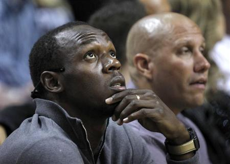Jamaica's sprinter Usain Bolt (L) looks on as the Miami Heat met the Boston Celtics during their NBA basketball game in Miami, Florida, October 30, 2012. REUTERS/Andrew Innerarity/Files