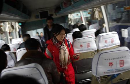 Shi Huaju reads a text message on her mobile phone as she boards a bus on the way home for Spring Festival in Chongqing January 29, 2013. REUTERS/Carlos Barria