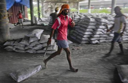 A labourer pulls a sack of cement along the floor after unloading it from a freight train at a railway station in Mumbai July 20, 2011. REUTERS/Danish Siddiqui/Files