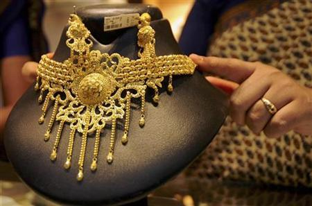 A saleswoman displays a gold necklace at a jewellery shop in Agartala, June 25, 2009. REUTERS/Jayanta Dey/Files