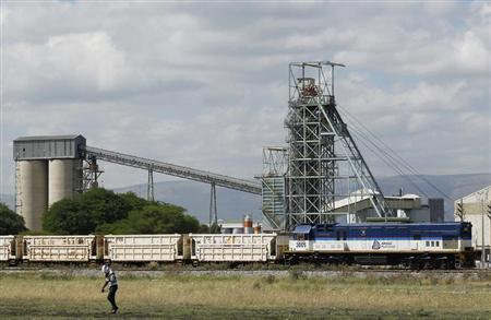 A man walks past a train carrying goods, at Anglo Platinum's Khomanani shaft 1 mine in Rustenburg, northwest of Johannesburg January 15, 2013. REUTERS/Siphiwe Sibeko
