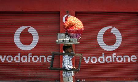 A vendor selling ''paani puri'', a traditional Indian snack, walks past closed shops displaying an advertisement for Vodafone in Jammu May 22, 2012. REUTERS/Mukesh Gupta/Files