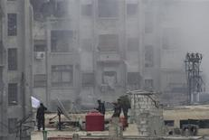 Integrantes do Exército Sírio Livre levantam bandeira islâmica no topo de um prédio depois de intensos confrontos com as forças do presidente Bashar al-Assad, na região de Jobar, em Damasco. 06/02/2013 REUTERS/Mohamed Dimashkia