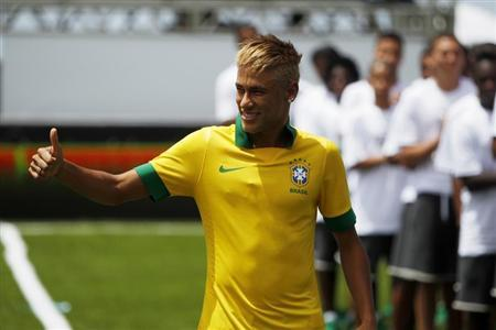 Brazil's national soccer player Neymar gives a thumbs up sign as he wears the new team jersey during its presentation at the Copacabana beach in Rio de Janeiro January 31, 2013. REUTERS/Pilar Olivares