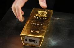Работник немецкого Бундесбанка тянется за слитком золота во время пресс-конференции во Франкфурте-на-Майне, 16 января 2013 года. Золотовалютные резервы РФ выросли на $2,8 миллиарда за неделю к 1 февраля благодаря положительной переоценке евро, тогда как все другие компоненты показывали отрицательную динамику. REUTERS/Lisi Niesner