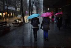 Two women carry umbrellas as they walk through hail on Bilbao's Gran Via February 6, 2013. REUTERS/Vincent West