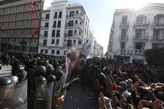Manifestantes tunisianos entram em confronto com a polícia durante protesto depois da morte de líder da oposição Chokri Belaid (no poster), diante do Ministério do interior, em Túnis. 06/02/2013 REUTERS/Anis Mili
