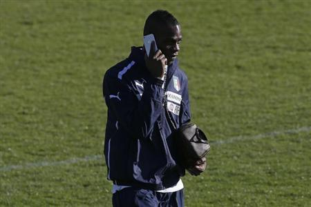 Italy's national soccer team player Mario Balotelli talks on his mobile phone as he arrives for a training session at Coverciano training centre near Florence February 4, 2013. REUTERS/Max Rossi