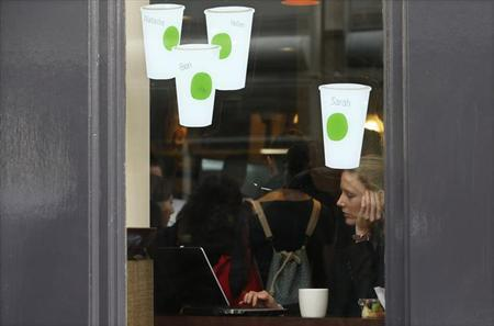 A woman looks at a laptop while sitting in a Starbucks in London October 24, 2012. REUTERS/Suzanne Plunkett/Files