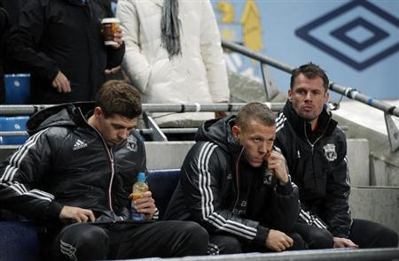 Liverpool's Steven Gerrard (L), Craig Bellamy (C) and Jamie Carragher sit on the bench during their English Premier League soccer match against Manchester City at the Etihad Stadium in Manchester, northern England, January 3, 2012. REUTERS/Phil Noble