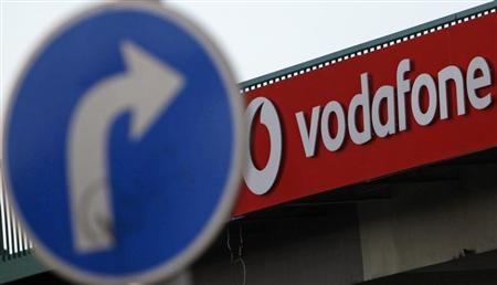 A traffic sign is seen next to the Vodafone logo in Prague February 7, 2012. REUTERS/David W Cerny