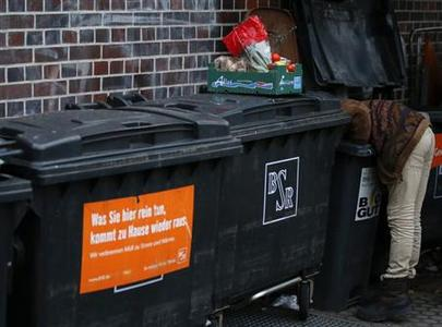 Benjamin Schmitt, a supporter of the foodsharing movement looks for food in a dumpster behind a supermarket in Berlin, January 31, 2013. REUTERS/Fabrizio Bensch