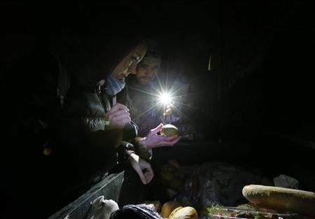 Benjamin Schmitt (R) and Helena Jachmann, supporters of the foodsharing movement sort through food found in a dumpster behind a supermarket in Berlin, February 4, 2013. REUTERS/Fabrizio Bensch