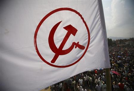 A party flag of the Unified Communist Party of Nepal (Maoist) flutters above the crowd during a mass gathering in Kathmandu June 15, 2012.REUTERS/Navesh Chitrakar