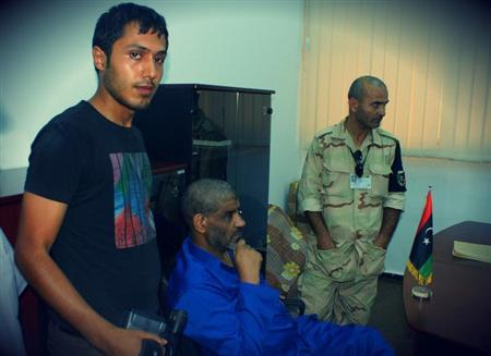 Muammar Gaddafi's former spy chief Abdullah al-Senussi (C) is seen in custody in Tripoli in this undated handout picture. Senussi was handed over to Libya by Mauritanian authorities after being captured in the West African state in March, triggering a tug of war between Libya, France and the ICC for his extradition. REUTERS/Libyan National Guard/Handout