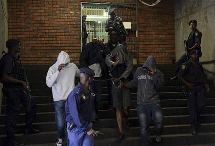 Members of the South African Tactical Response Team stand guard as some of the 19 arrested Congolese appear at a Pretoria court February 7, 2013. REUTERS/Stringer