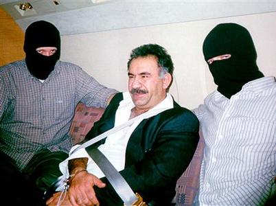 Turkish special team members wearing balaclavas sit next to bound and handcuffed Kurdish rebel leader Abdullah Ocalan aboard a private plane as he is flown in Turkey after he was captured in Kenya's capital Nairobi in this early February 15, 1999 file photo. REUTERS/Handout/Files