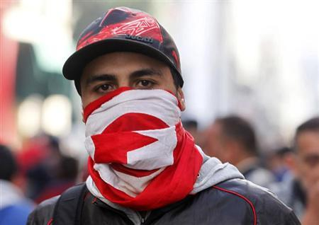 A protester wears a Tunisian flag during a demonstration in Tunis February 7, 2013. Tunisian police fired teargas on Thursday to disperse hundreds of people protesting near the Interior Ministry in Tunis against the Wednesday killing of secular opposition leader Chokri Belaid, a Reuters witness said. REUTERS/Louafi Larbi (TUNISIA - Tags: POLITICS CIVIL UNREST)