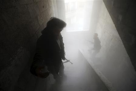 Free Syrian Army fighters walk through a dust-filled stairwell after a comrade fired a B-10 recoilless rifle at Syrian Army soldiers in the Haresta neighbourhood of Damascus February 7, 2013. REUTERS/Goran Tomasevic