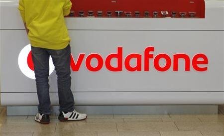 A customer stands next to the Vodafone logo in a shopping mall in Prague February 7, 2012. REUTERS/David W Cerny