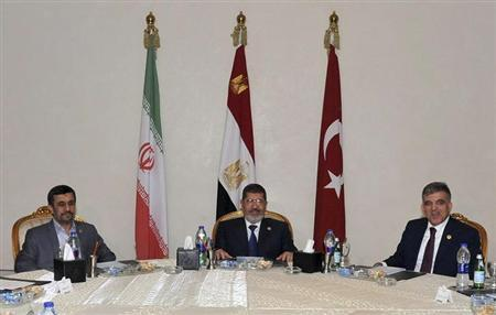 Egyptian President Mohamed Mursi (C) attends a meeting with Turkish President Abdullah Gul and Iran's President Mahmoud Ahmadinejad after the opening of the Organisation of Islamic Cooperation (OIC) summit in Cairo February 6, 2013. REUTERS/Egyptian Presidency/Handout