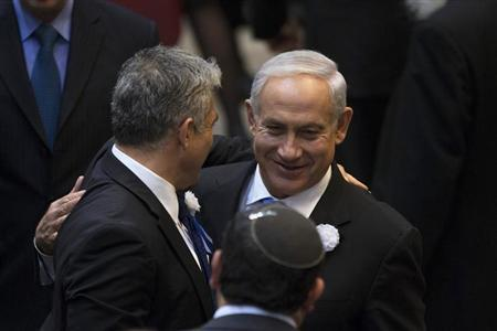 Israel's Prime Minister Benjamin Netanyahu (R) and Yair Lapid, head of Yesh Atid (There is a Future) party embrace after the swearing-in ceremony of the 19th Knesset, the new Israeli parliament, in Jerusalem February 5, 2013. REUTERS/Ronen Zvulun