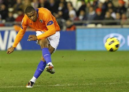 Malaga's Julio Baptista shoots to score a goal against Valencia during their Spanish first division soccer match at the Mestalla Stadium in Valencia January 22, 2011. REUTERS/Heino Kalis/Files