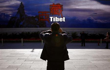 A man takes a photograph in front of a screen displaying propaganda about China's Tibet Autonomous Region on Beijing's Tiananmen Square November 12, 2012. REUTERS/David Gray/Files