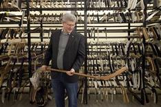 Canadian Prime Minister Stephen Harper holds a hockey stick from the 1907 Stanley Cup final during a research visit to the Hockey Hall of Fame in Toronto in this December 2011 handout photo obtained by Reuters February 7, 2013. Harper has recently completed a book about the history of hockey that will be published by Simon & Schuster in the United States and Canada in November 2013. REUTERS/Jason Ransom/PMO/Handout