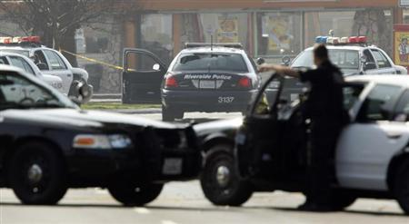A police officer protects the scene, where two Riverside Police officers were shot while in their car (C), in the early morning in Riverside, California February 7, 2013. REUTERS/Alex Gallardo