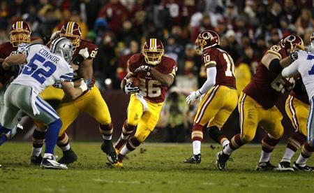 Washington Redskins running back Alfred Morris (C) runs through the Dallas Cowboys line during the first half of their NFL football game in Landover, Maryland, December 30, 2012. REUTERS/Jonathan Ernst