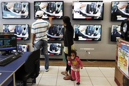 A couple with their daughter, look at flat-screen television sets at a Casas Bahia store in Sao Paulo February 7, 2013. REUTERS/ Nacho Doce