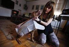 Karen Varley, a flight attendant and design student at New York's Fashion Institute of Technology (FIT) who owns PJNYDogwear.com, a maker of fashions for dogs, measures her pit bull Sugar for a custom sweater in her New York City apartment February 7, 2013. REUTERS/Mike Segar