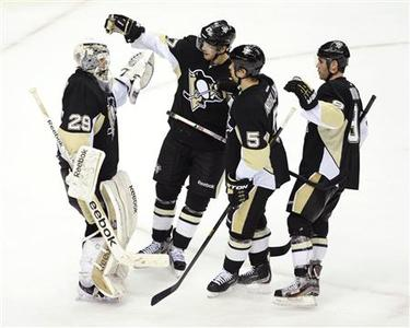 Pittsburgh Penguins goaltender Marc-Andre Fleury (29) is congratulated by teammates Simon Despres (47), Deryk Engelland (5) and Pascal Dupuis (9) after his NHL hockey game victory against the Washington Capitals in Pittsburgh, Pennsylvania, February 7, 2013. REUTERS/David A. DeNoma