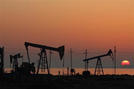 Oil derricks are silhouetted against the rising sun on an oilfield in Baku, January 24, 2013. REUTERS/David Mdzinarishvili