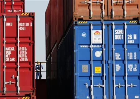 A worker is seen in a container area at a port in Tokyo November 21, 2012. REUTERS/Issei Kato/Files