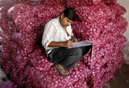 A trader works on his accounts while sitting on sacks of onions at a wholesale market in Ahmedabad February 4, 2013. REUTERS/Amit Dave