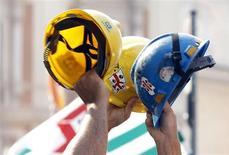 Operai sollevano i loro elmetti da lavoro. REUTERS/Alessandro Bianchi