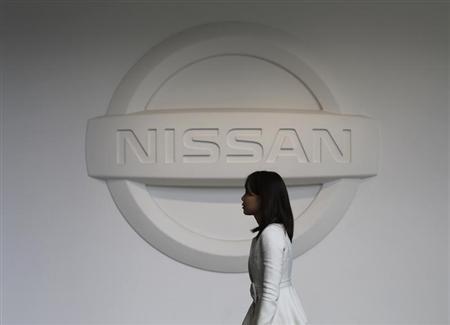 A woman walks past the logo of Nissan Motor Co at the company's showroom in Yokohama, south of Tokyo February 8, 2013. REUTERS/Toru Hanai