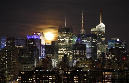 The moon rises behind the skyline of midtown Manhattan in New York as seen from Jersey City, New Jersey January 27, 2013. REUTERS/Gary Hershorn