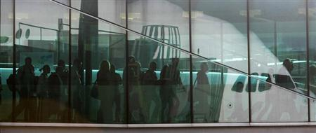 Passengers walk across an air bridge as they disembark a flight at Changi Airport in Singapore May 13, 2009. REUTERS/Vivek Prakash