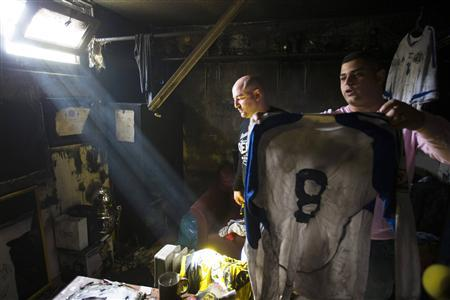 An employee of Israeli Premier League side Beitar Jerusalem holds up a shirt that was damaged along with other items in a suspected arson attack at the soccer team's club house in Jerusalem February 8, 2013. REUTERS/Ronen Zvulun