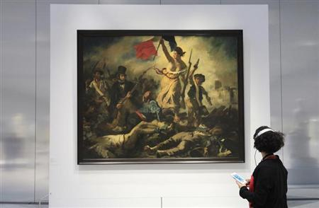 A woman looks at Eugene Delacroix 's painting, ''Liberty Leading the People (28 July 1830) (La Liberté guidant le peuple) in ''La Galerie du Temps'' (Gallery of Time) during media day on the eve of the inauguration of the Le Louvre Lens Museum, in Lens, northern France, December 3, 2012. REUTERS/Pascal Rossignol/Files