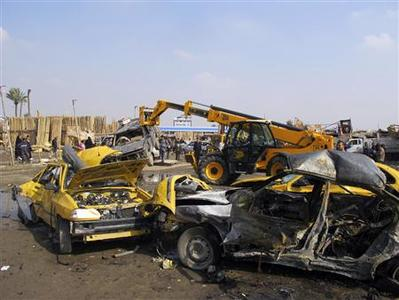 Iraqi security personnel and residents gather at the site of a car bomb attack in Baghdad's Kadhimiya district February 8, 2013. REUTERS/Thaier Al-Sudani