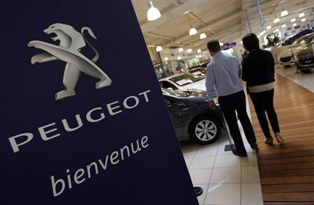 A salesman speaks with a customer next to a Peugeot car at a dealership in Marseille February 1, 2013. REUTERS/Jean-Paul Pelissier (FRANCE - Tags: TRANSPORT BUSINESS)