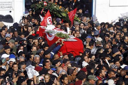 Mourners carry the coffin of slain opposition leader Chokri Belaid during his funeral procession towards the nearby cemetery of El-Jellaz, where he is to be buried, in the Jebel Jelloud district of Tunis February 8, 2013. Tens of thousands of mourners chanted anti-Islamist slogans on Friday at the Tunis funeral of secular opposition leader Belaid, whose assassination has plunged Tunisia deeper into political crisis. REUTERS/Anis Mili (TUNISIA - Tags: POLITICS CIVIL UNREST CRIME LAW TPX IMAGES OF THE DAY)