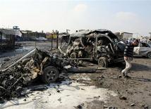 Мужчина стоит около сгоревших автомобилей после взрыва бомбы в Багдаде 8 февраля 2013 года. По меньшей мере 26 человек погибли в результате серии взрывов на рынках в Ираке, целью которых стали мусульмане-шииты, сообщила полиция и источники в больницах в пятницу. REUTERS/Thaier Al-Sudani